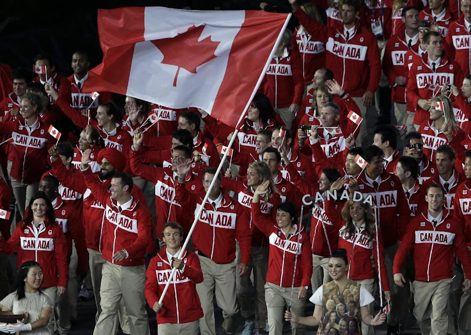 Canada's Simon Whitfield carries the flag during the Opening Ceremony at the 2012 Summer Olympics, Friday, July 27, 2012, in London. (AP Photo/Paul Sancya)