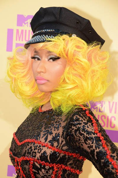 Nicki Minaj tucked her cotton candy peach, yellow and lime green curls under a rhinestone-adorned officer's cap and accessorized with inches-long lashes, pale pink lips, a lacey black dress and a sult