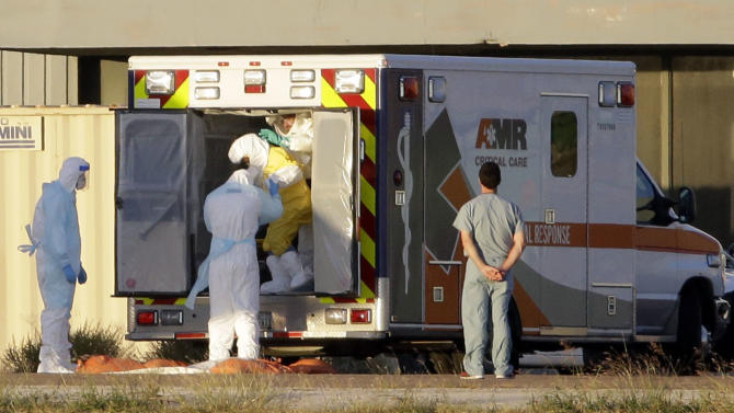 Medical staff in protective gear escort Nina Pham, exiting the ambulance, to a nearby aircraft at Love Field, Thursday, Oct. 16, 2014, in Dallas. Pham, a nurse at Texas Health Presbyterian Hospital Dallas, was diagnosed with the Ebola virus after caring for Thomas Eric Duncan who died of the same virus. (AP Photo/Tony Gutierrez)