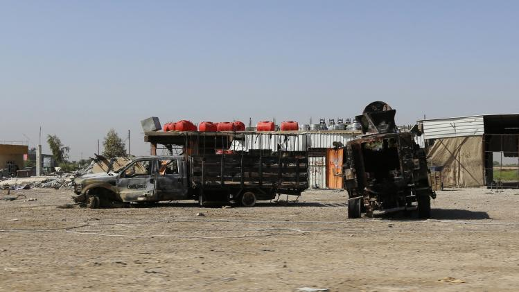 Burnt vehicles belonging to the Iraqi security forces are seen on a road leading to Samarra at Salahuddin province