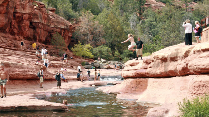 This undated photo courtesy of Arizona State Parks shows visitors swimming at Slide Rock State Park in Ariz. Considered one of the nation's top swimming holes, Slide Rock Park features a natural chute where swimmers can slide down the slippery bottom and some great spots along the creek to just wade or swim.    (AP Photo/Arizona State Parks)