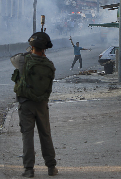 A Palestinian demonstrator holds rocks as he stands facing an Israeli border police officer, during clashes at the Qalandia checkpoint between the West Bank city of Ramallah and Jerusalem, Wednesday, Sept. 21, 2011. Palestinians clashed with Israeli security forces in Qalandia Wednesday, as thousands of flag-waving Palestinians rallied in towns across the West Bank to show support for their president's bid to win U.N. recognition of a Palestinian state. (AP Photo/Tara Todras-Whitehill)
