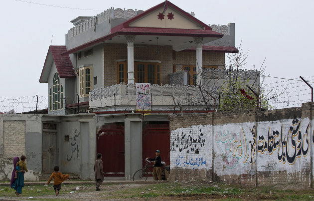 In this photo taken Thursday, March 8, 2012, Afghan refugees gather outside the house in Haripur, Pakistan, that Pakistan's intelligence agency believes Osama bin Laden lived in for nearly a year unti