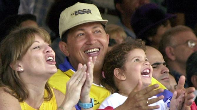 FILE - In this July 15, 2001 file photo, Venezuela's President Hugo Chavez, center, his wife Marisabel with their daughter Rosa Ines watch a parade on Children's Day in Caracas, Venezuela. Venezuela's Vice President Nicolas Maduro announced on Tuesday, March 5, 2013 that Chavez has died at age 58 after a nearly two-year bout with cancer. During more than 14 years in office, Chavez routinely challenged the status quo at home and internationally. He polarized Venezuelans with his confrontational and domineering style, yet was also a masterful communicator and strategist who tapped into Venezuelan nationalism to win broad support, particularly among the poor.  (AP Photo/Ivan Gonzalez, File)