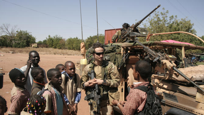 A French soldier talks with young residents of San in central Mali, as French troops pass through en route to Sevare, Mali, Friday, Jan. 18, 2013. French forces encircled a key Malian town on Friday to stop radical Islamists from striking closer to the capital, a French official said. The move to surround Diabaly came as French and Malian authorities said they had retaken Konna, the central city whose capture prompted the French military intervention last week.(AP Photo/Harouna Traore)