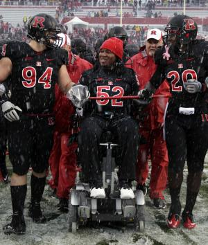 FILE - This Oct. 29, 2011 file photo shows paralyzed former Rutgers football player Eric LeGrand (52), center in wheelchair, coming onto the field with players Scott Vallone (94) and Khaseem Greene (20), before an NCAA college football game against West Virginia in Piscataway, N.J. Rutgers will retire the jersey number of LeGrand. Scarlet Knights coach Kyle Flood made the announcement Tuesday, July 30, 2013, during football media day for the American Athletic Conference. (AP Photo/Mel Evans, File)