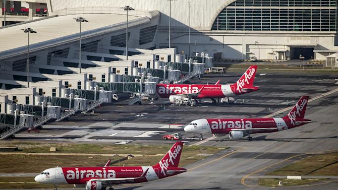 CORRECTS NUMBERS OF PASSENGERS ON BOARD - In this Nov 26, 2014 photo, AirAsia Airbus A320-200 passenger jets are parked on the tarmac at low cost terminal KLIA2 in Sepang, Malaysia. An AirAsia plane with 162 people on board lost contact with ground control on Sunday, Dec. 28, 2014, while flying over the Java Sea after taking off from a provincial city in Indonesia for Singapore, and search and rescue operations were underway. The planes in this photo are not the plane that went missing while flying from Indonesia to Singapore but one of the same models. (AP Photo/Vincent Thian)