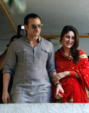 Bollywood stars Saif Ali Khan, left, and Kareena Kapoor step out on a balcony to greet waiting fans after getting married in Mumbai, India, Tuesday, Oct. 16, 2012. The Press Trust of India reported the couple married Tuesday in a small official ceremony in Khans house in Mumbai with a few friends and family members in attendance. (AP Photo/ Rajanish Kakade)