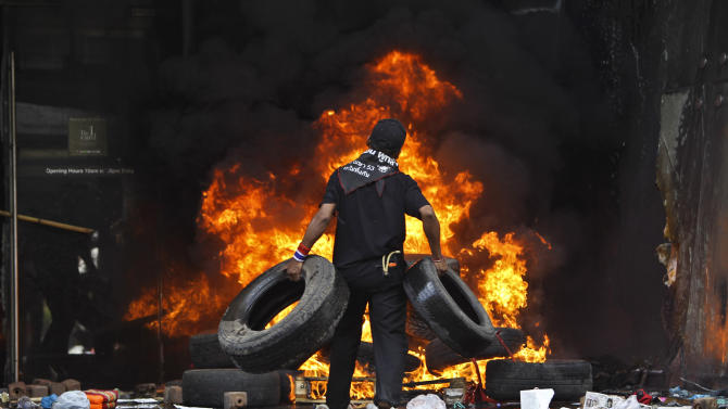FILE - In this May 19, 2010 file photo, an anti-government protestor piles tires on a fire at Central World shopping mall in Bangkok. Just two years ago, Thailand was at war with itself. Rifle shots and exploding grenades rang out in Bangkok as troops crushed through barricades to disperse a nine-week-old insurrection. (AP Photo/Wally Santana, File)