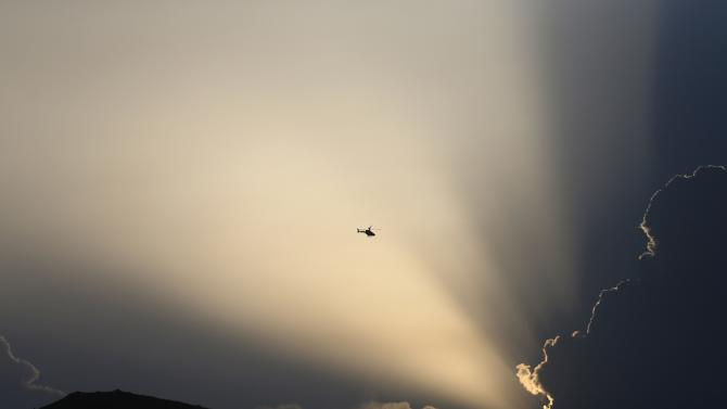 A NATO helicopter flies overhead Kabul International Airport, during an attack on the airport in Kabul