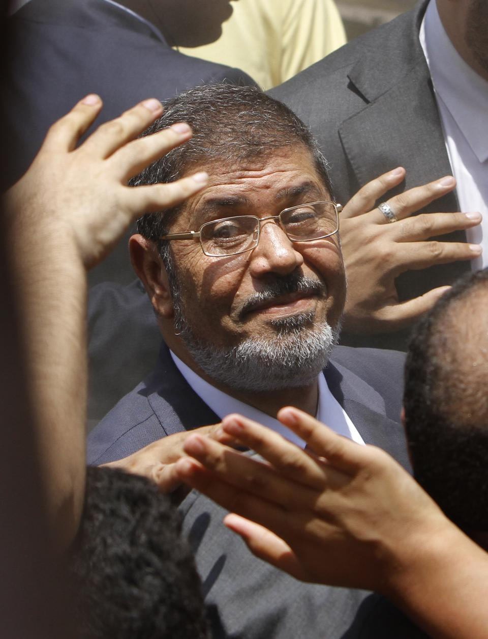 FILE - In this Saturday, June 16, 2012 file photo, supporters wave to Egyptian presidential candidate Mohammed Morsi after he cast his vote at a polling station in Zagazig, 63 miles (100 kilometers) northeast of Cairo, Egypt. (AP Photo/Amr Nabil, File)
