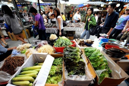 <p>People walk past a vegetable stall in Namdaemun market in Seoul. South Korea's inflation rate was the lowest for more than 12 years in August, official figures showed Monday, raising prospects of an imminent interest rate cut.</p>