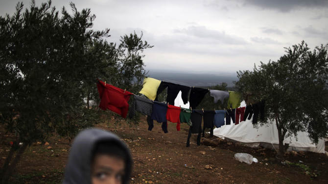 In this Monday, Dec. 10, 2012 photo, a Syrian boy who fled his home with his family walks back to his tent, next to laundry hung on olive trees, at a camp for displaced Syrians, in the village of Atmeh, Syria. This tent camp sheltering some of the hundreds of thousands of Syrians uprooted by the country's brutal civil war has lost the race against winter: the ground under white tents is soaked in mud, rain water seeps into thin mattresses and volunteer doctors routinely run out of medicine for coughing, runny-nosed children. (AP Photo/Muhammed Muheisen)
