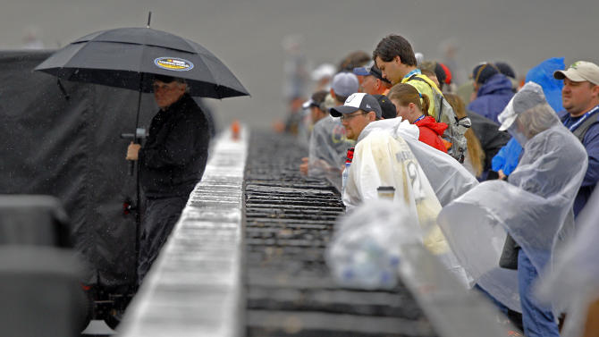 Fans brave the rain as they get a chance to look at cars before a NASCAR Sprint Cup Series auto race at Bristol Motor Speedway on Sunday, April 19, 2015, in Bristol, Tenn. (AP Photo/Wade Payne)