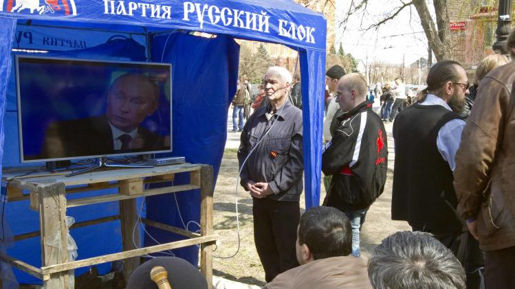 Pro-Russian supporters watch a television broadcast of Russian President Vladimir Putin, in their camp near the seized office of the SBU state security service in Luhansk