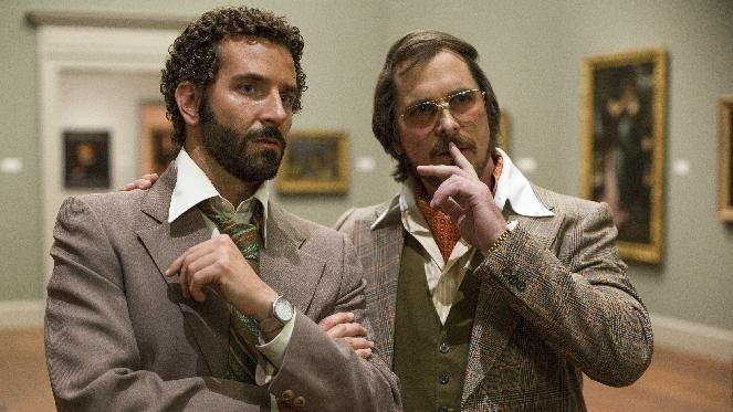 """This film image released by Sony Pictures shows Bradley Cooper, left, and Christian Bale in a scene from """"American Hustle."""" The New York Film Critics Circle named """"American Hustle"""" the best film of 2013, giving David O. Russell's fictionalized Abscam tale an early jolt in Hollywood's awards season. (AP Photo/Sony - Columbia Pictures, Francois Duhamel)"""