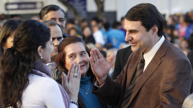 Paraguay's new President Federico Franco blesses a youth during a Mass outside the Cathedral in Asuncion, Paraguay, Saturday, June 23, 2012. Former President Fernando Lugo's ouster by lawmakers on Friday has been widely condemned in Latin America as Franco is promising to honor foreign commitments and reach out to Latin American leaders to try to keep his country from becoming a regional pariah. (AP Photo/Jorge Saenz)