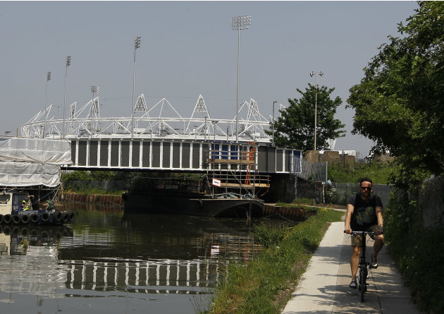 A cyclist passes by the Olympic Stadium on a canal side cycle path in London, Thursday, May 24, 2012. There are many cycle paths across London that can be used to travel the capital. Like a runner or