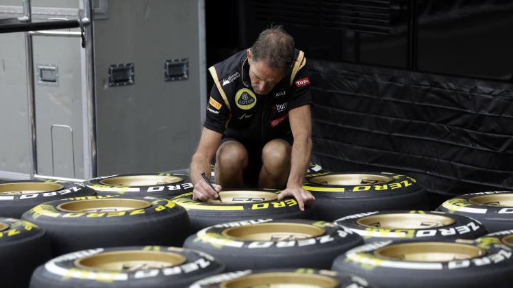 A Lotus mechanic writes on a tire in the paddock at the Spa-Francorchamps circuit, Belgium, Thursday, Aug. 21, 2014. The Belgium Formula One Grand Prix will be held on Sunday. (AP Photo/Luca Bruno)