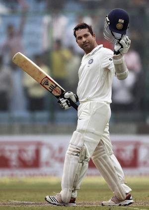 Indian batsman Sachin Tendulkar celebrates after he completed 15,000 runs in test cricket on the third day of the first of three test match series between India and West Indies, in New Delhi, India, Tuesday, Nov. 8, 2011. (AP Photo) INDIA OUT