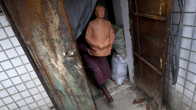 A worker carries a wax mould of China's late Chairman Mao Zedong as he walks out of a factory which produces statues of Mao in Shaoshan