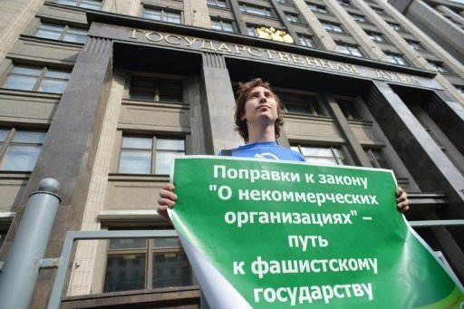 "<p>An activist holds a poster outside Russia's lower house of parliament in Moscow on July 6, against a proposed bill forcing NGOs who receive funding from abroad to register as ""foreign agents"". The poster reads: ""The NGO bill will lead to lead to a Fascist State!"". Russian President Vladimir Putin has signed into law the controversial bill passed by parliament, the Kremlin said Saturday.</p>"