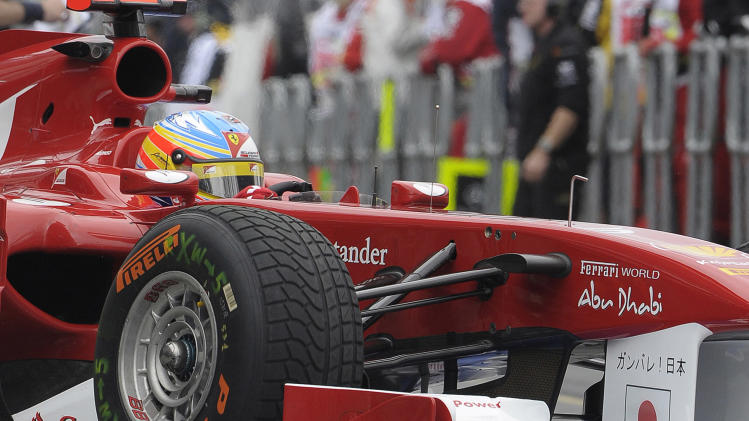 Fernando Alonso of Spain in a Ferrari pulls into in his garage during the first practice session ahead of the Australian F1 GP in Melbourne, Australia, Friday, March 25, 2011. Both Ferrari cars are sporting a Japanese flag in support for the tsunami earthquake tragedy. (AP Photo/Rob Griffith)