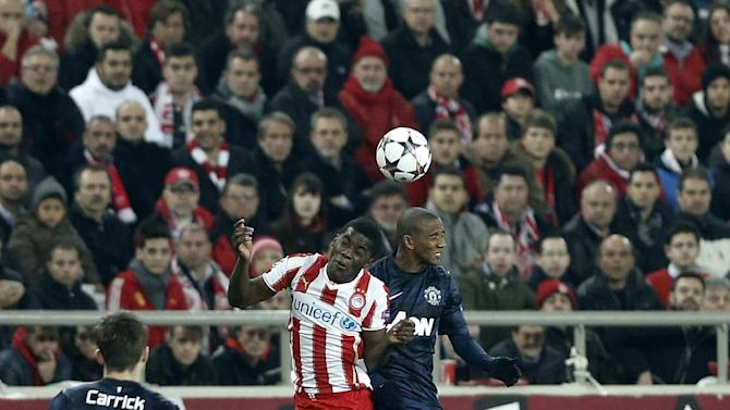 Olympiakos' Joel Campbell fights for a header with Manchester United's Ashley Young during their Champions League, round of 16, first leg soccer match at Georgios Karaiskakis stadium, in Piraeus port, near Athens, on Tuesday, Feb. 25, 2014