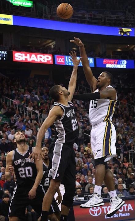 Utah Jazz's Derrick Favors (15) takes a shot as San Antonio Spurs' Tim Duncan (21) defends in the second half of an NBA basketball game on Saturday, Dec. 14, 2013, in Salt Lake City. San Anton
