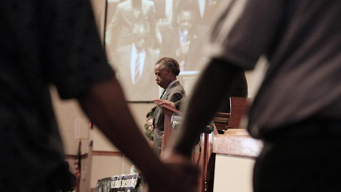 Rev. Al Sharpton, center, listens as The Rev. Jesse Jackson, not seen, leads a prayer during a community forum at the Macedonia Baptist Church in Eatonville, Fla., Monday, March 26, 2012. Students also held rallies on the campus of Florida A&M University in Tallahassee and outside the Seminole County Criminal Justice Center, where prosecutors are reviewing the case to determine if charges should be filed.  (AP Photo/Julie Fletcher)