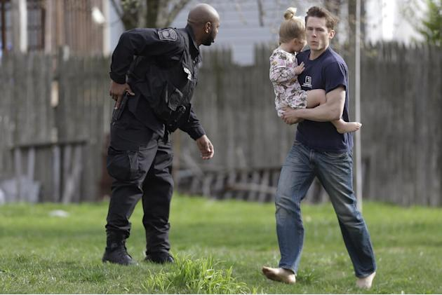 A police officer evacuates a shoeless man holding a child as members of law enforcement conduct a search for a suspect in the Boston Marathon bombings, Friday, April 19, 2013, in Watertown, Mass.  The