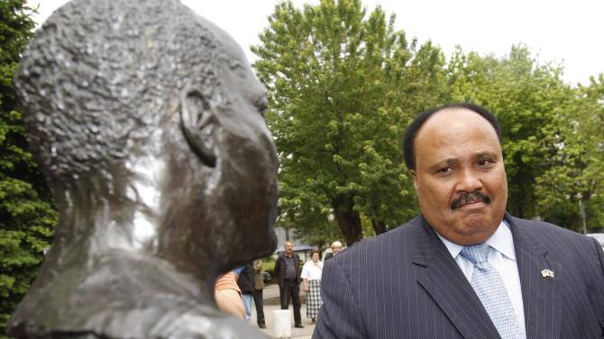 "FILE - In this Wednesday, May 13, 2009 file photo, Martin Luther King III visits the statue of his father the Rev. Dr. Martin Luther King Jr., during his visit to the Bosnian town of Tuzla, 72 kilometers (45 miles) north of Bosnian capital of Sarajevo. King arrived in a five-day visit to Bosnia during which he is scheduled to hold several lectures and visit different locations promoting activities of the ""Realizing Dreams"" organization over which he presides. (AP Photo/Amel Emric, File)"