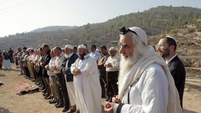 FILE- In this Nov. 11, 2010 file photo, Rabbi Menachem Froman, foreground, prays with Muslim worshippers during a joint Muslim-Jewish prayer for rain near a water spring in the West Bank village of Walajeh. Rabbi Menachem Froman, an Israeli settler known for his efforts to promote coexistence between Arabs and Jews, died Monday Feb. 4, 2013, after a long illness. He was 68. (AP Photo/Nasser Shiyoukhi, File)