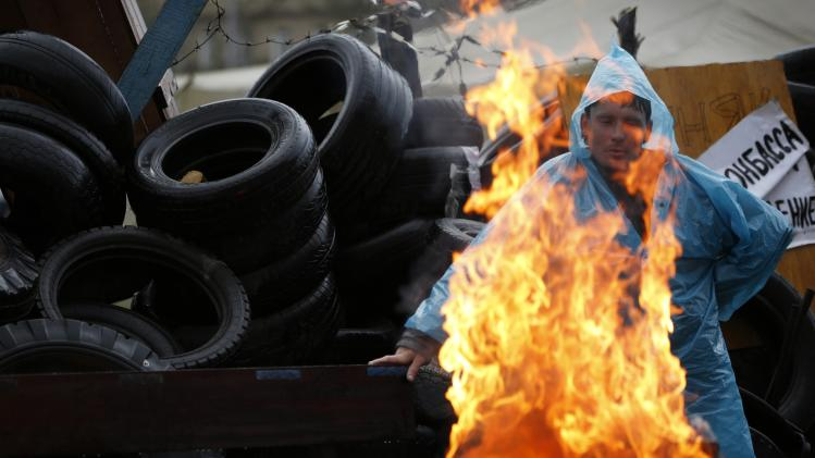 A pro-Russia protester warms himself by the fire on a barricade outside a regional government building in Donetsk