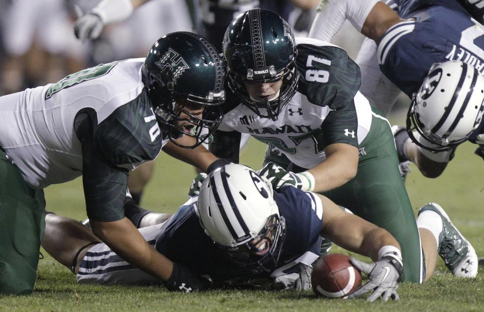 A Brigham Young player dives onto a fumble as Hawaii offensive linesman Frank Loyd Jr. (70) and tight end Ryan Hall (87) watch during the third quarter of an NCAA college football game Friday, Sept. 28, 2012, in Provo, Utah. (AP Photo/Rick Bowmer)