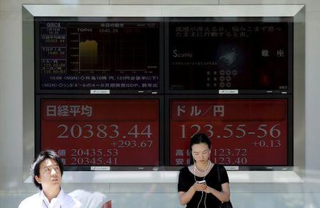 People stand in front of electronic boards showing Japan's Nikkei average and the exchange rates between the Japanese yen against the U.S. dollar outside a brokerage in Tokyo