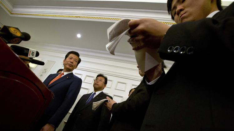 Natsuo Yamaguchi, left, leader of the New Komeito party from Japan, briefs journalists at a hotel in Beijing Friday, Jan. 25, 2013. (AP Photo/Ng Han Guan)