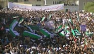 An image from the Syrian opposition Shaam News Network shows people carrying the coffins of people said to have been killed during an offensive by government troops in Daraa. The new head of Syria&#39;s main opposition group called Sunday for mass defections from a Syrian regime struggling to survive by carrying out massacres, as the death toll in the uprising topped 14,000