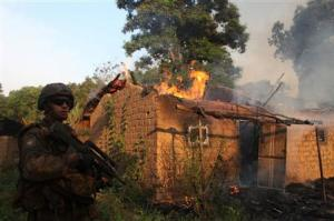 A French soldier patrols past a house on fire at a village in Bossangoa