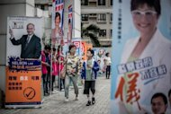 A woman and a child walk past election flags displayed in a street of Hong Kong. Hong Kong voted Sunday in legislative elections seen as a test for the pro-Beijing government, after it was forced to scrap mandatory Chinese patriotism classes in the face of escalating protests