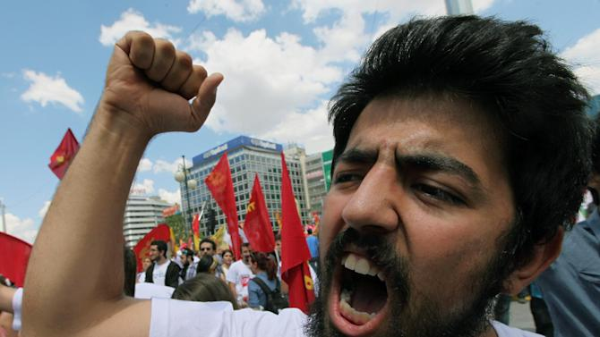 """A Turkish protester shouts slogans such as """"don't yield """" as thousands of trade union members who are on a two-day strike march to Kizilay Square, Ankara, Turkey, Wednesday, June 5, 2013. In Ankara and Istanbul some demonstrations were largely jovial and humorous, calling themselves """"looters,"""" asked Turkey's prime minister Recep Tayyip Erdogan to resign. (AP Photo/Burhan Ozbilici)"""