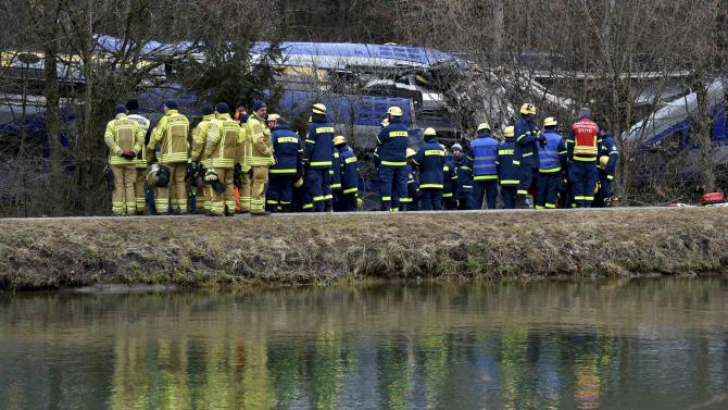 Rescue workers stand in front of two crashed trains near Bad Aibling