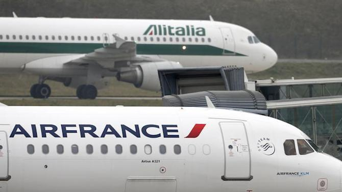 An Alitalia plane passes an Air France plane on the tarmac of Charles de Gaulles International Airport in Roissy