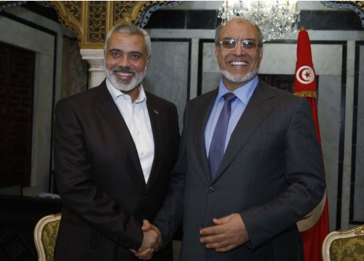 Tunisia's Prime Minister Hamadi Jbeli shakes hands with senior Hamas leader Ismail Haniyeh in Tunis