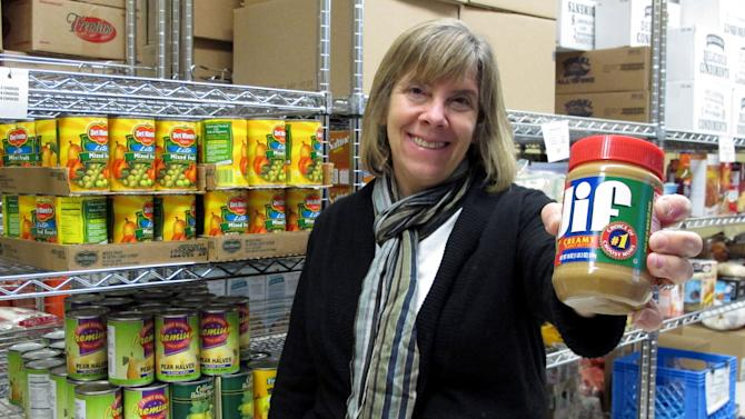 In this Nov. 9, 2011, photo manager Kathy Kelly-Long holds a jar of peanut butter which is in short supply at the Broad Street Presbyterian Church food pantry in Columbus, Ohio. Food banks around the country say rising peanut butter prices are making it harder for them to provide one of their most-requested items this holiday season. (AP Photo/Kantele Franko)