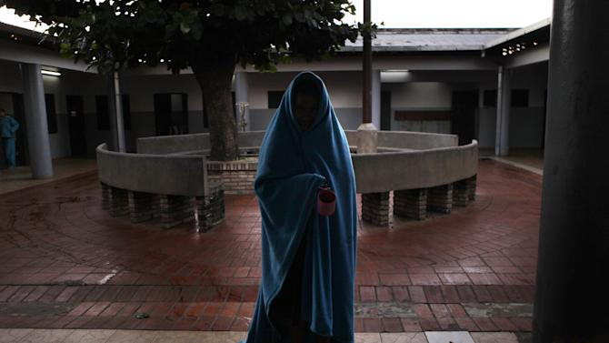 In this May 319, 2013 photo, a female patient at the Neuro-Psychiatric Hospital wears a blanket in the courtyard before breakfast in Asuncion, Paraguay. Despite the center's questionable conditions, for many patients it remains the only option. Doctors say 75 percent of the hospital's patients have been abandoned by their families. Many feel lucky to receive any kind of medical treatment, even if the system is broken. (AP Photo/Jorge Saenz)