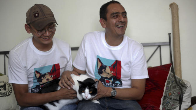 "Diego Cruz, left, and Sergio Chamorro pose with their cat Morris, in their home in Xalapa, Mexico, Saturday, June 15, 2013. Put forth as candidate by Camacho and a group of friends after they became disillusioned with the empty promises of politicians, Morris, a black-and-white cat with orange eyes, is running for mayor of Xalapa in eastern Mexico with the campaign slogan ""Tired of Voting for Rats? Vote for a Cat."" And he is attracting tens of thousands of politician-weary, two-legged supporters on social media. (AP Photo/Felix Marquez)"