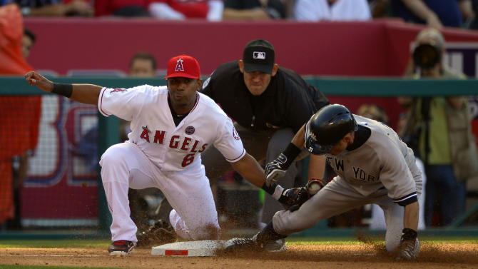 New York Yankees' Ichiro Suzuki, right, is tagged out at third by Los Angeles Angels third baseman Alberto Callaspo while trying to steal during the fourth inning of their baseball game on Saturday, June 15, 2013, in Anaheim, Calif. (AP Photo/Mark J. Terrill)
