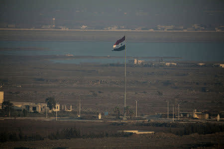 A Syrian flag flutters in Syria close to the border fence with the Israeli-occupied Golan Heights