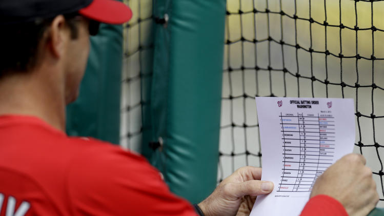 St. Louis Cardinals manager Mike Matheny holds the Washington Nationals line up before an exhibition spring training baseball game, Saturday, March 2, 2013, in Jupiter, Fla. (AP Photo/Julio Cortez)